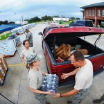 Louisiana Air National Guardsmen, Senior Airman Hunni B. Bolton and Senior Airman Gary Martin, both of the 259th Air Traffic Control Squadron, load commodities into the back of a resident's vehicle