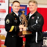 METAIRIE, La. - Louisiana National Guardsman Staff Sgt. Kenneth Carrigee, Recruiting and Retention Command noncommissioned officer, awards Archbishop Rummel High School football head coach Jay Roth with the MaxPreps Tour of Champions trophy in honor of their winning season, in the Rummel high school gym, Jan. 18. The Rummel Raiders went undefeated in their 2012 season and became the number one high school football team in the state. (National Guard photo by Spc. Tarell J. Bilbo, Recruiting and Retention Command Public Affairs Representative/RELEASED)